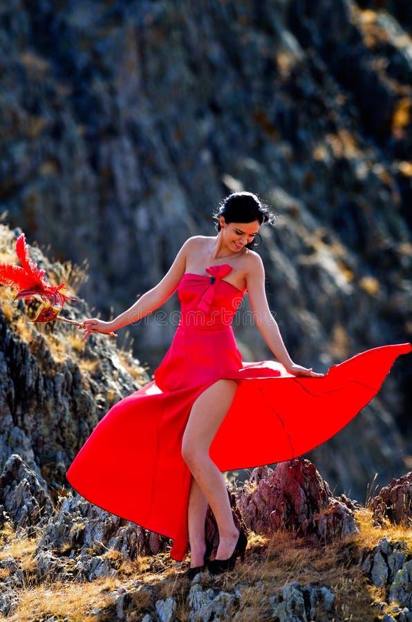 Młoda kobieta jest ubranym długą czerwieni suknię, maskę i obraz stock