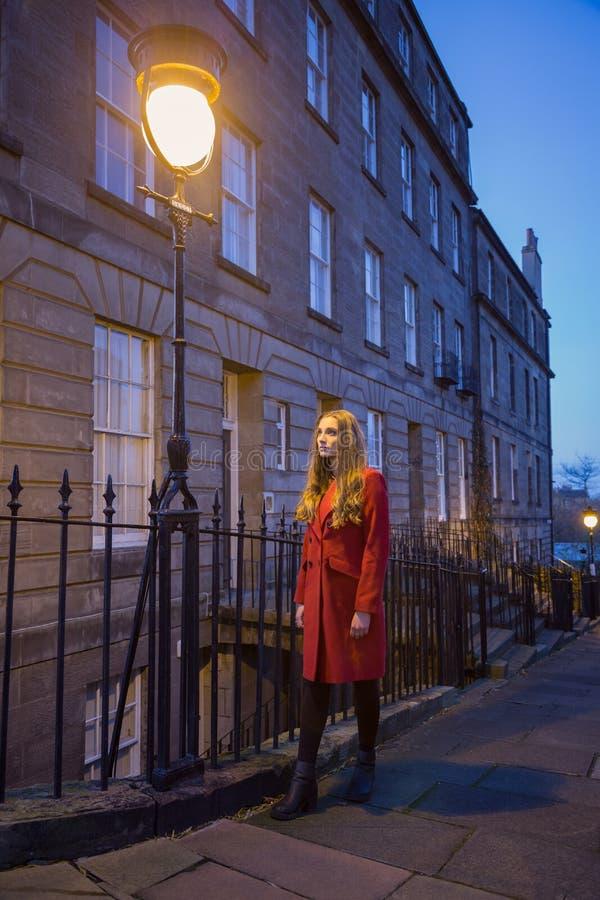 Młoda kobieta jest ubranym długą czerwoną kurtkę pod latarnią uliczną obrazy stock