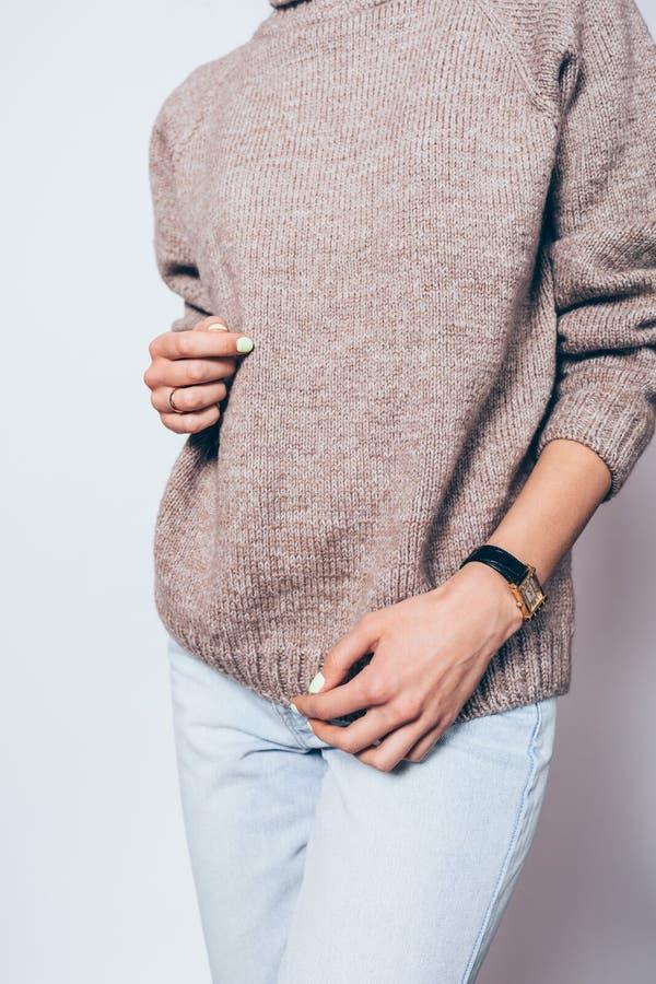Młoda kobieta jest ubranym eleganckiego dużych rozmiarów brązu pulower zdjęcia royalty free