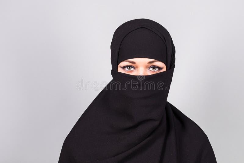 Młoda kobieta jest ubranym niqab na tle zdjęcia stock