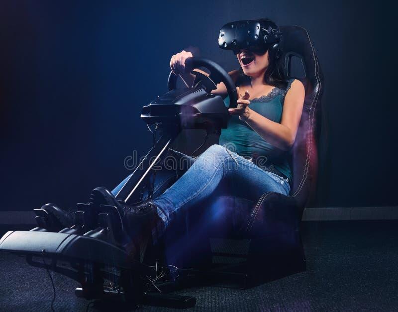 Młoda kobieta jest ubranym VR słuchawki ma zabawę podczas gdy jadący na samochodowy ścigać się symulanta kokpicie z siedzeniem i  obraz royalty free