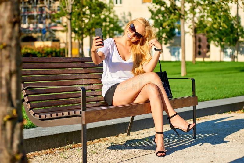 Młoda kobieta jest usytuowanym na ławce i bierze selfies obrazy royalty free