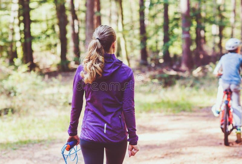 Młoda kobieta jogging ćwiczenia w pogodnym lesie i robi zdjęcia stock