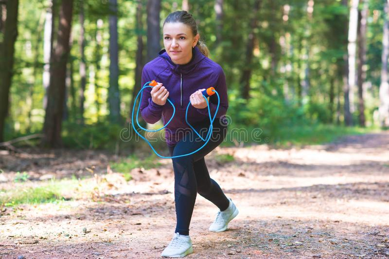 Młoda kobieta jogging ćwiczenia w pogodnym lesie i robi zdjęcia royalty free