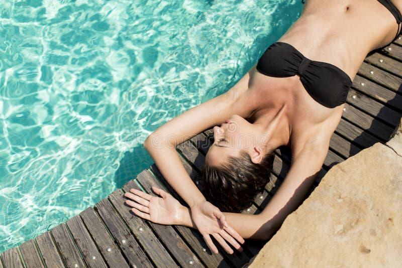 Młoda kobieta kłaść basenem zdjęcia stock