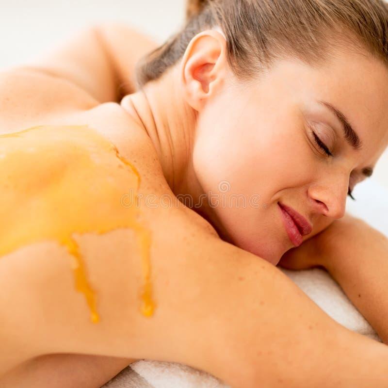 Młoda kobieta kłaść na masażu stole z miodem na plecy obraz stock