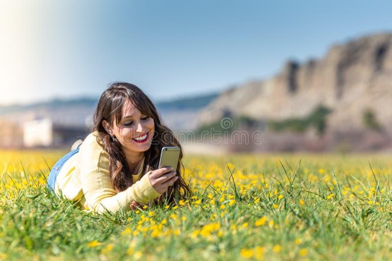 Młoda Kobieta Kłaść W dół Używać telefon komórkowego zdjęcie stock
