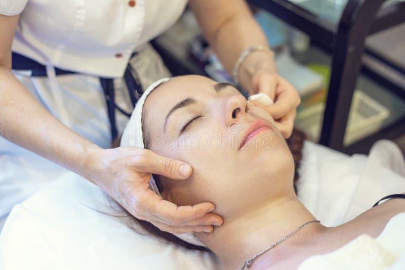 Młoda kobieta kłama na leżance przy fachową cosmetologist i dermatologa kliniką Kobiety lekarka czyści skórę na twarzy fotografia stock