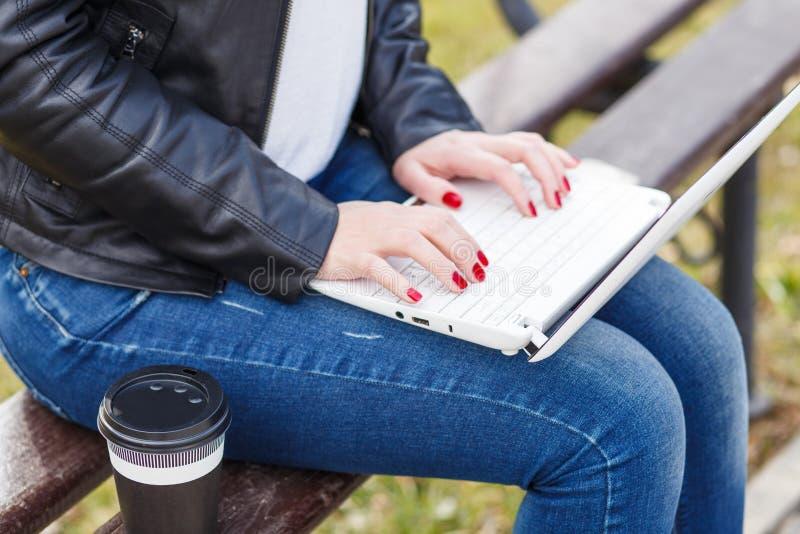 Młoda kobieta kawowej przerwy obsiadanie z laptopem fotografia royalty free