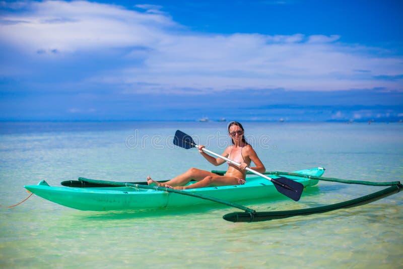 Młoda kobieta kayaking samotnie w jasnym błękitnym morzu obrazy stock
