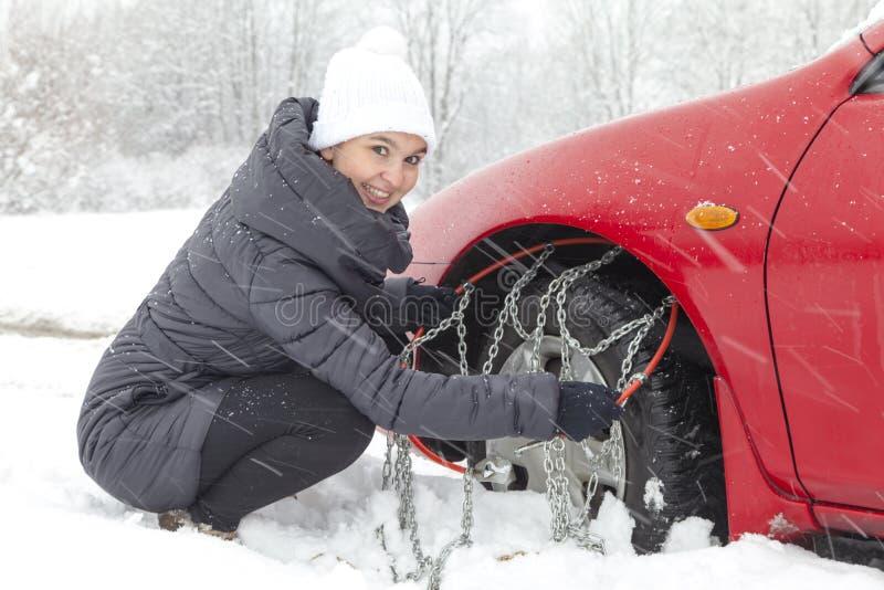 Młoda kobieta kierowcy montażu opony samochodowi łańcuchy zdjęcie royalty free