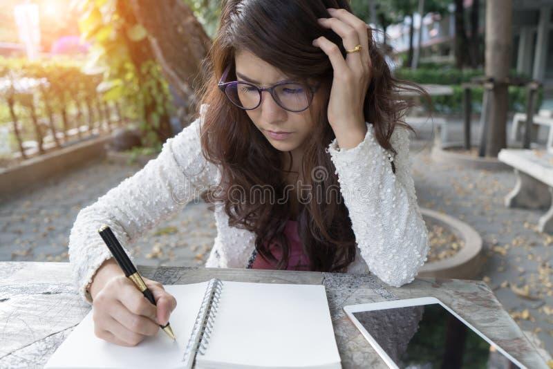 Młoda kobieta koncentrata czytelnicza książka dziewczyna uczenie writing dom obraz stock