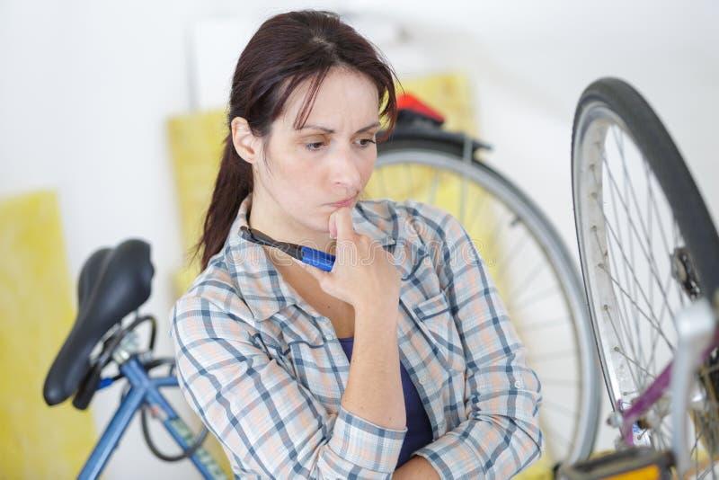 Młoda kobieta koncentruje na łamanym bicyklu obraz royalty free