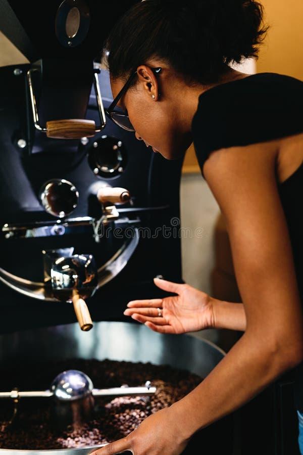 Młoda kobieta kontroluje proces prażak kawę obraz royalty free