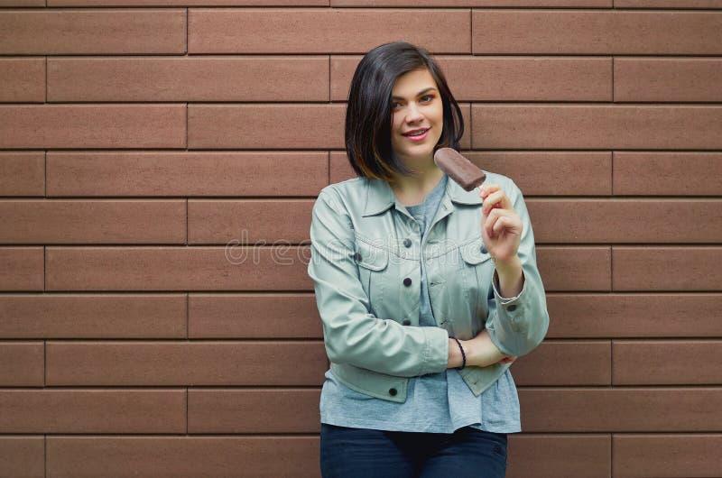 młoda kobieta kosztuje lody w czekoladowym glazerunku obraz stock