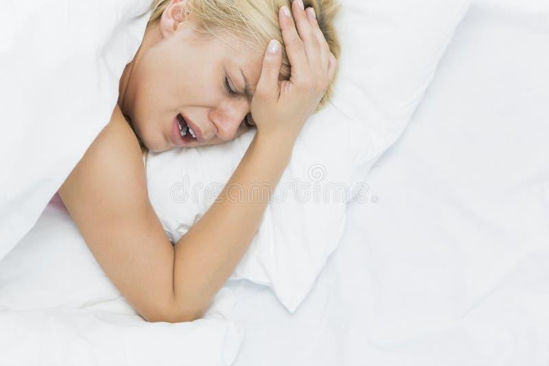 Młoda kobieta krzyczy podczas gdy cierpiący od migreny w łóżku zdjęcie royalty free
