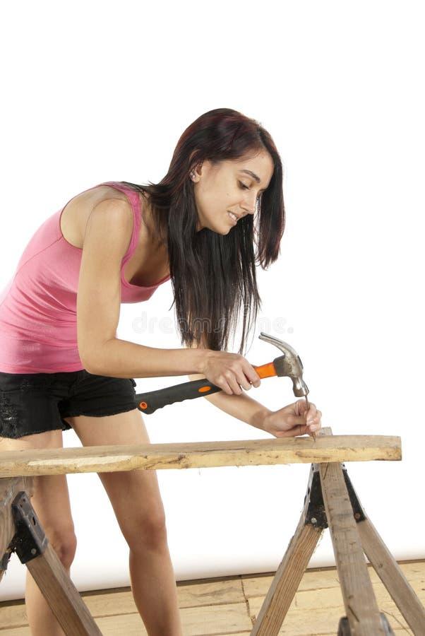 Młoda kobieta młotkuje gwóźdź w drewno zdjęcia royalty free