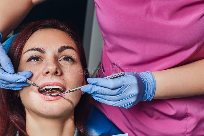 Młoda kobieta ma egzamin w dentysty krześle z rozpieczętowanym usta podczas gdy siedzący obrazy royalty free