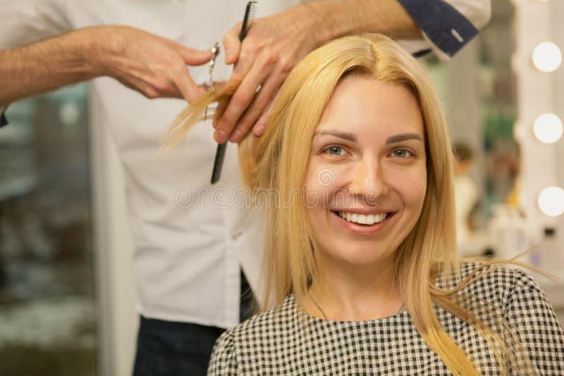 Młoda kobieta ma jej włosy projektującego fryzjerem obrazy stock