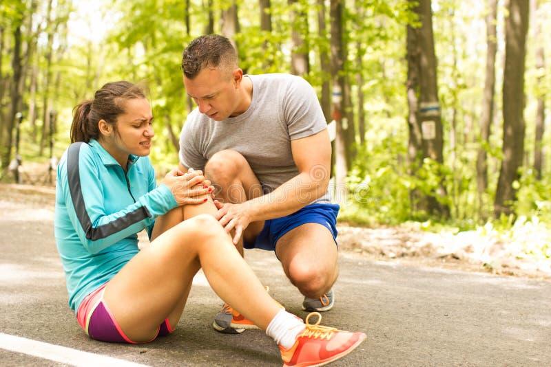 Młoda kobieta ma uraz kolana outside w pogodnym podczas gdy jogging fotografia stock