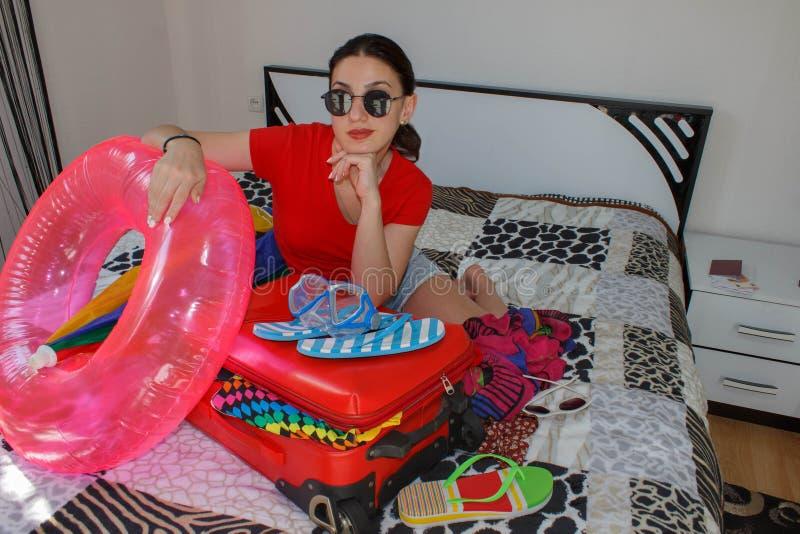 Młoda kobieta marzy światowy wycieczki obsiadanie Dziewczyny kocowania walizki na podłoga w domu zdjęcia stock