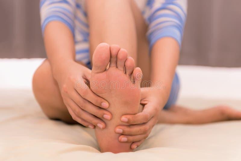 Młoda kobieta masuje jej stopę na łóżku fotografia royalty free