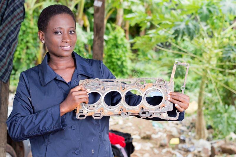 Młoda kobieta mechanik trzyma uszkadzającą samochodową część obrazy royalty free