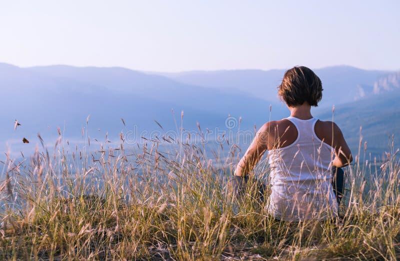 Młoda kobieta medytująca na wierzchołku góra obrazy royalty free