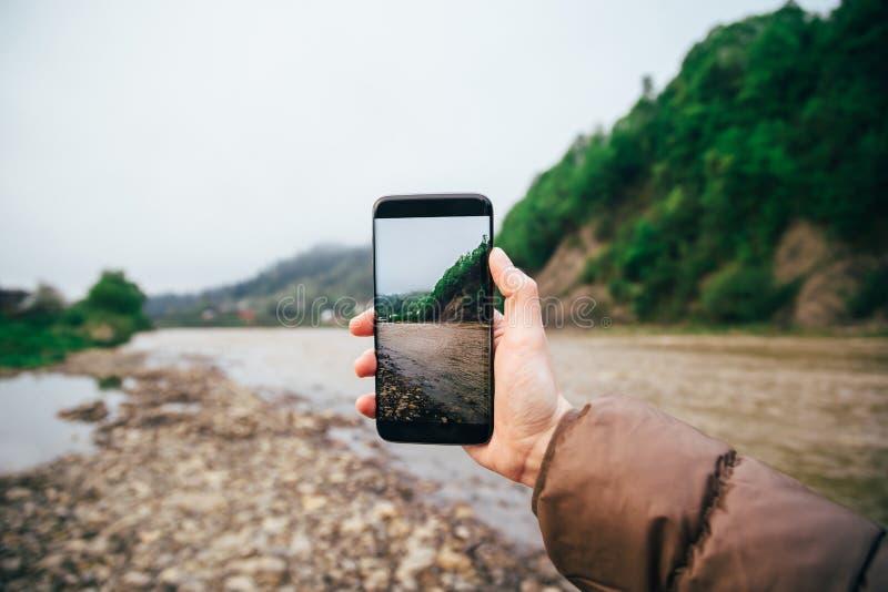 Młoda kobieta modniś robi fotografii góry i rzeki krajobraz na smartphone kamerze, część na interneta socjalny środkach zdjęcie royalty free