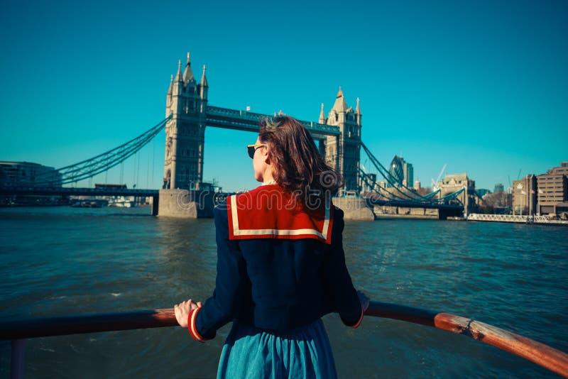 Młoda kobieta na łódkowatym patrzeje wierza moscie zdjęcie royalty free