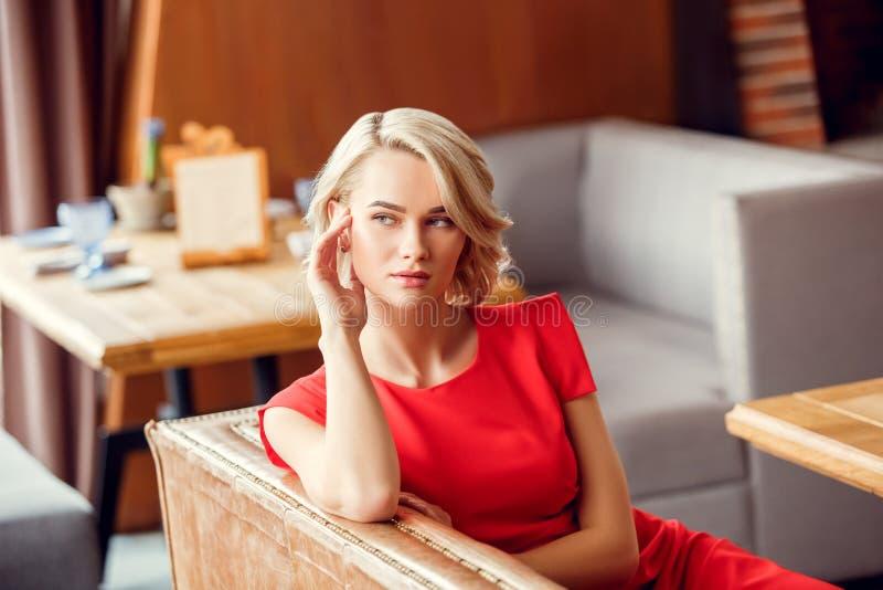 Młoda kobieta na dacie w restauracyjny siedzący patrzeć na boku rozważny zdjęcie royalty free