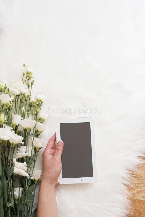 Młoda kobieta na drewnianej podłoga na białym futerkowym dywanie przy wygodnym domem i chwytami pastylka w jego ręce Wielkiego bu obrazy royalty free