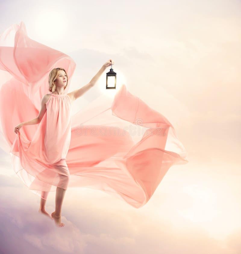 Młoda kobieta na fantazi chmurnieje z antykwarską lampą obrazy stock
