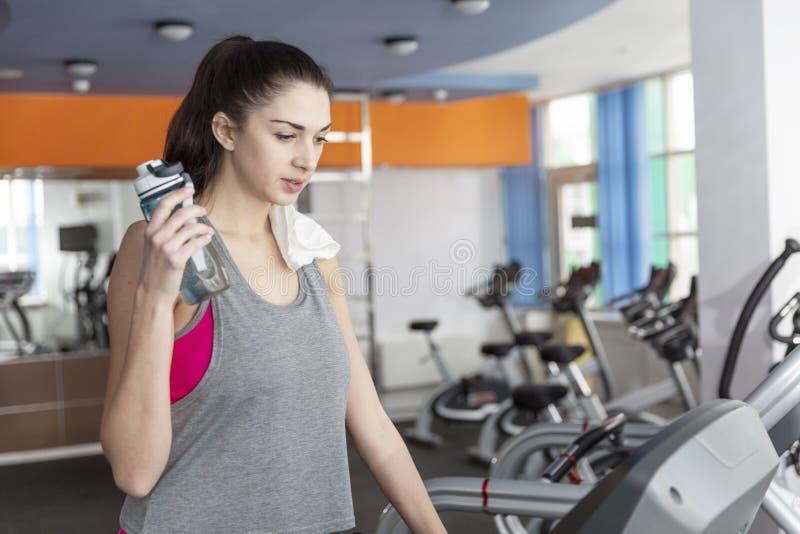 Młoda kobieta na karuzeli w gym Z ręcznikiem na jego ramieniu i butelką woda w jego ręce obrazy stock
