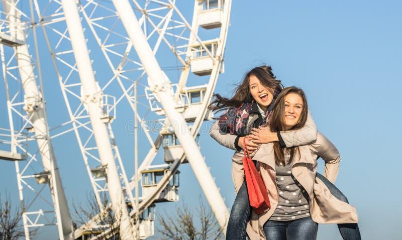 Młoda kobieta najlepsi przyjaciele cieszy się czas wraz z piggyback przy Luna parka ferris kołem zdjęcie stock