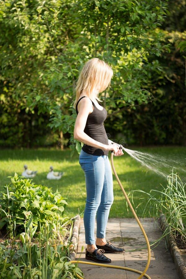 Młoda kobieta nalewa jej ogród zdjęcie royalty free