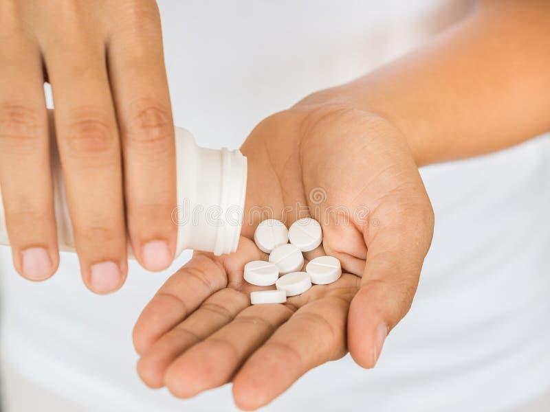Młoda kobieta nalewa out medycynę, kapsułę lub pigułkę, w jej rękę H obraz stock