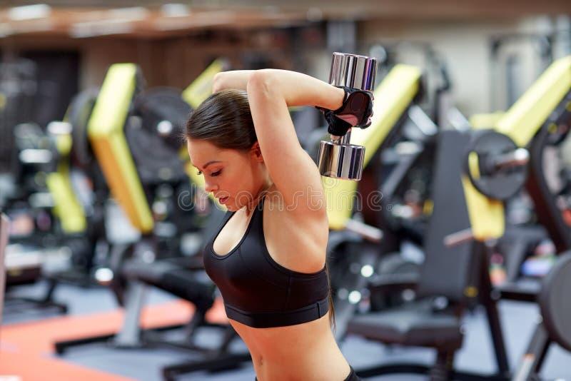 Młoda kobieta napina mięśnie z dumbbell w gym zdjęcie royalty free