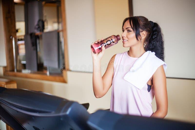 Młoda kobieta napoju czysta woda w sprawności fizycznej gym zdjęcie royalty free