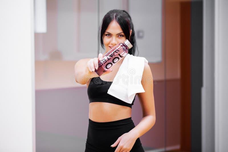 Młoda kobieta napoju czysta woda w sprawności fizycznej gym fotografia stock
