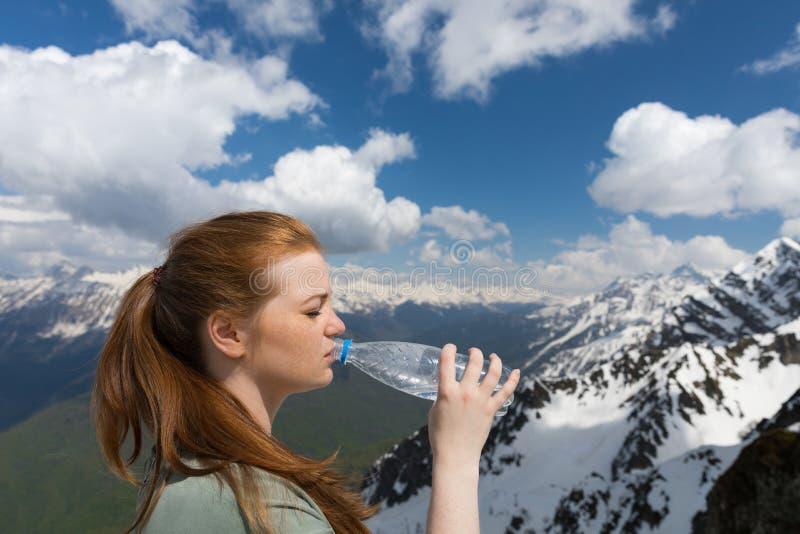 Młoda kobieta napoju woda od plastikowej butelki w górach na śniegu osiąga szczyt tło obrazy royalty free