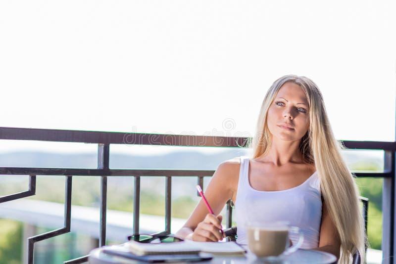 Młoda kobieta napoju writing w nutowej książki czasopiśmie w caf i kawa zdjęcia stock