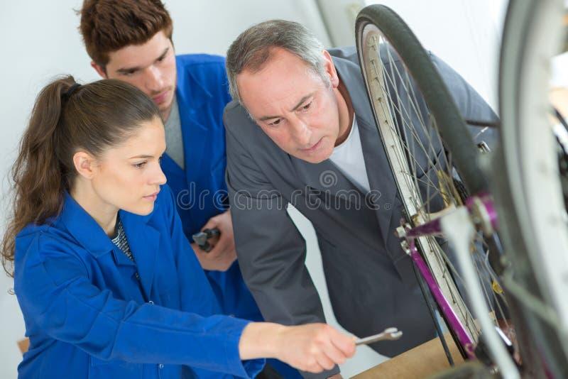 Młoda kobieta naprawia rowerowego koło obraz royalty free