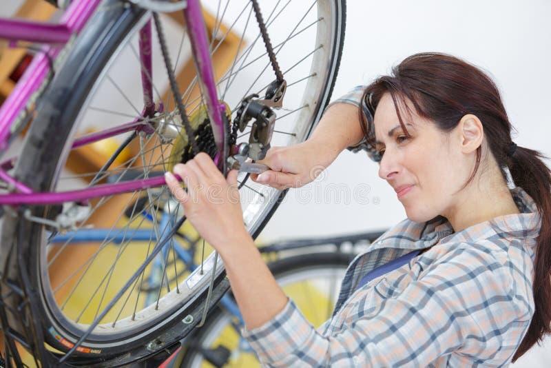 Młoda kobieta naprawia rowerowego koło fotografia royalty free