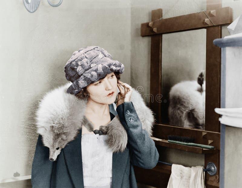Młoda kobieta niesie lis etolę na ona i przystosowywa jej kolczyka ramiona (Wszystkie persons przedstawiający no są długiego utrz zdjęcie stock