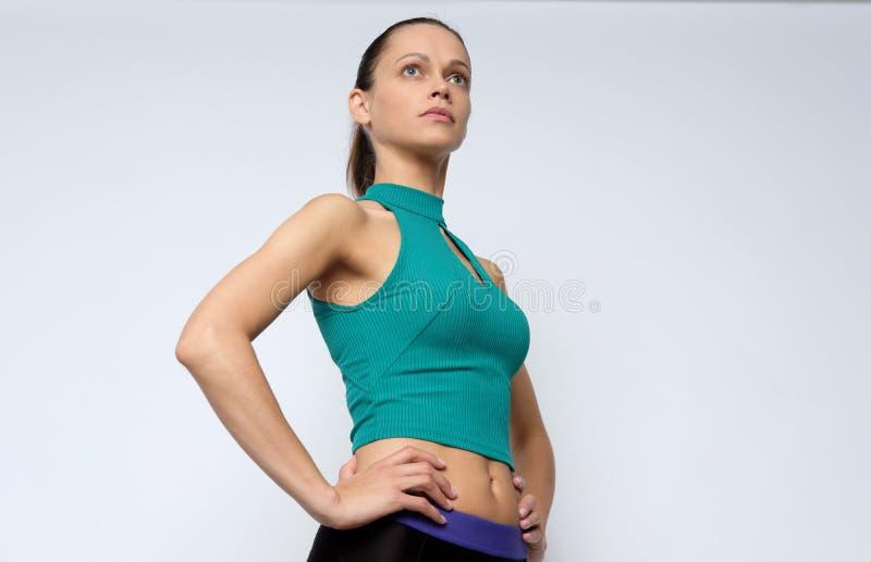 MÅ'oda kobieta nosi ubrania sportowe izolowane na szarym fotografia stock