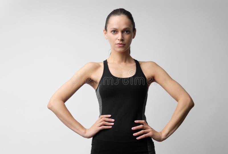 MÅ'oda kobieta nosi ubrania sportowe izolowane na szarym zdjęcia stock