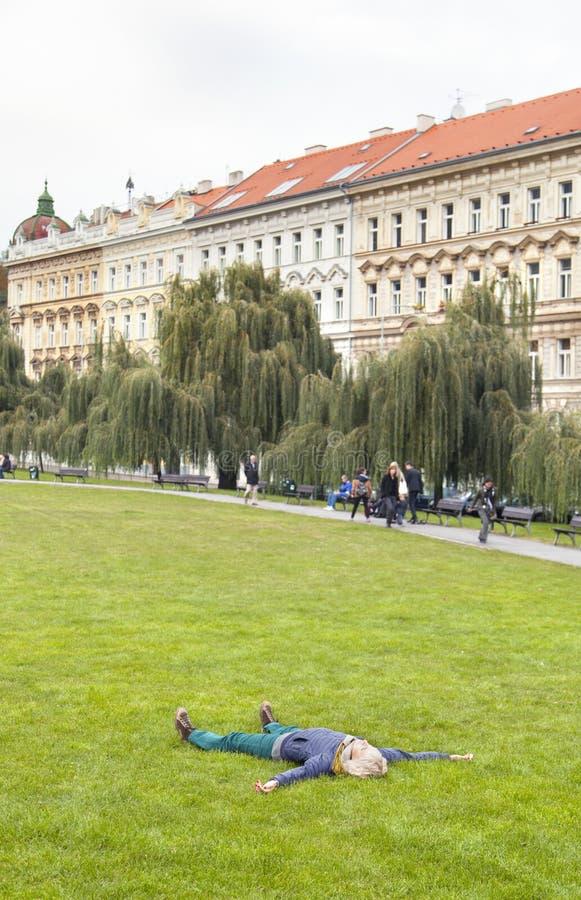 Młoda kobieta odpoczywa kłaść na trawie w miasto parku zdjęcie stock