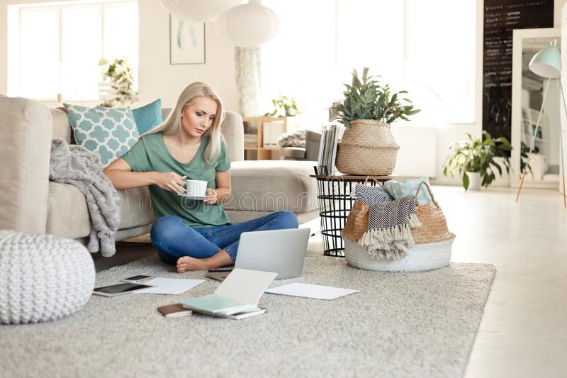 Młoda kobieta odpoczywa w domu, pije kawowy i używa laptop, zdjęcie royalty free