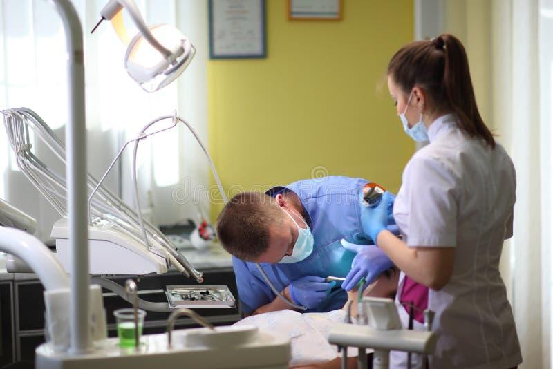 Młoda kobieta odwiedza dentysty przy kliniką Męski dentysta z pacjentem w klinice obrazy stock